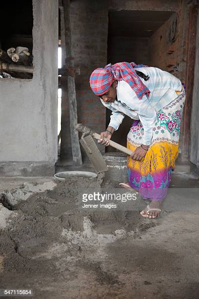 Indian woman, construction worker mixing cement
