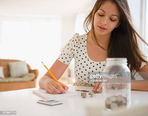 Indian woman counting coins and writing on notepad