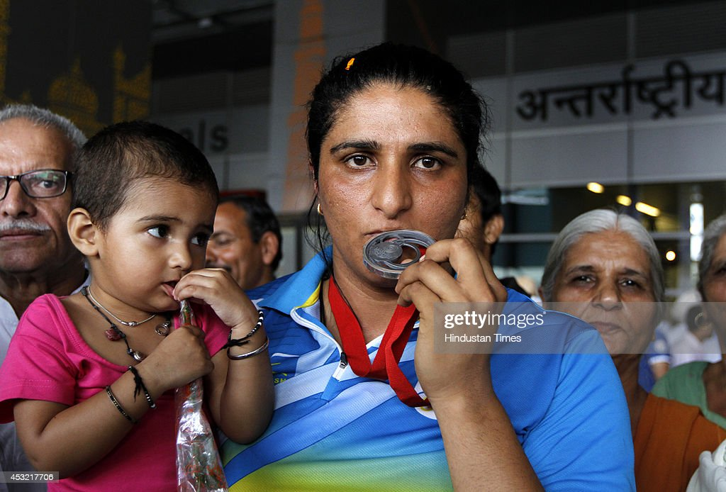 Indian woman discus thrower Seema Punia poses with her Silver medal on her arrival at the IGI Airport after participating in CWG 2014 held at Glasgow on August 5, 2014 in New Delhi, India.