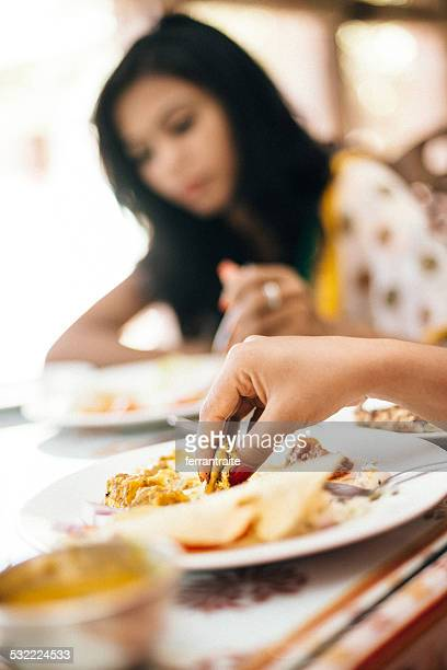 Indian Woman Eating with hands in Restaurant