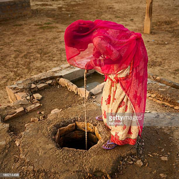 Indian woman getting water from the well. Rajasthan, Thar desert