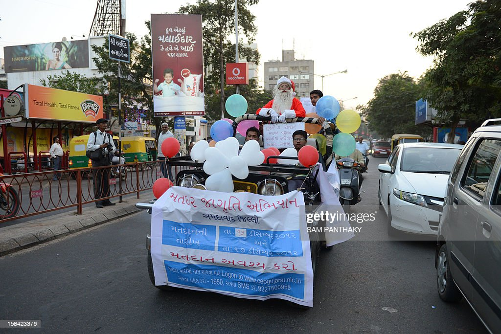 Indian woman Harshaben Prajapati, dressed as Santa Claus, rides a jeep while spreading awareness on voting in Ahmedabad on December 16, 2012. The second phase of voting for India's Gujarat state will be held December 17. AFP PHOTO / Sam PANTHAKY