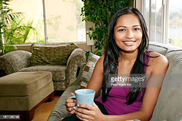 Indian woman having cup of coffee on sofa