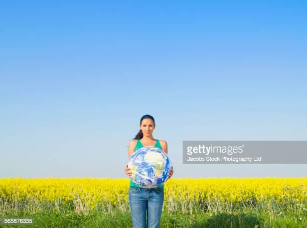 Indian woman holding globe in field of flowers