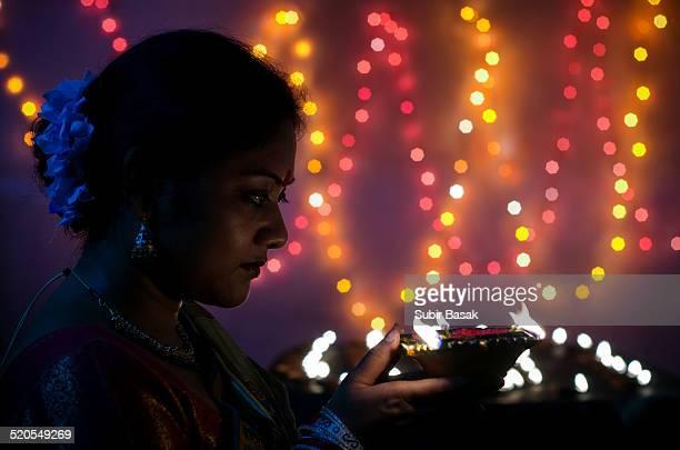 Indian woman holding  lit oil lamp during Diwali