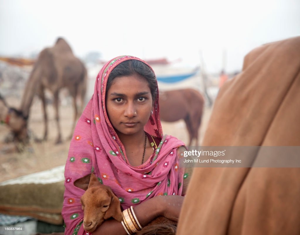 Indian woman holds a goat during the Pushkar Camel Fair