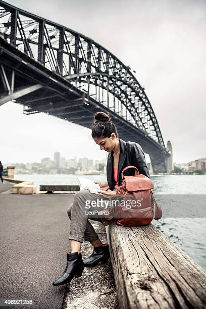 Indian woman in the city of Sydney reading a book