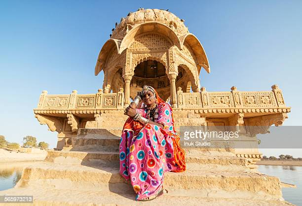 Indian woman in traditional clothes sitting near monument, Jaisalmer, Rajasthan, India