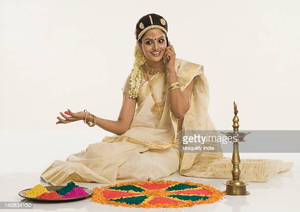 Indian woman in traditional clothing making rangoli and talking on a mobile phone
