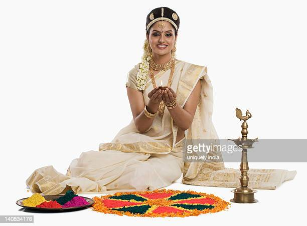 Indian woman in traditional clothing praying with an oil lamp at Durga puja festival