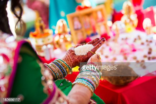 Indian woman in traditional garb with handful of rice : Stock Photo