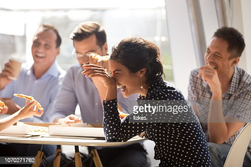 Indian woman laughing eating pizza with diverse coworkers in office : Stock Photo