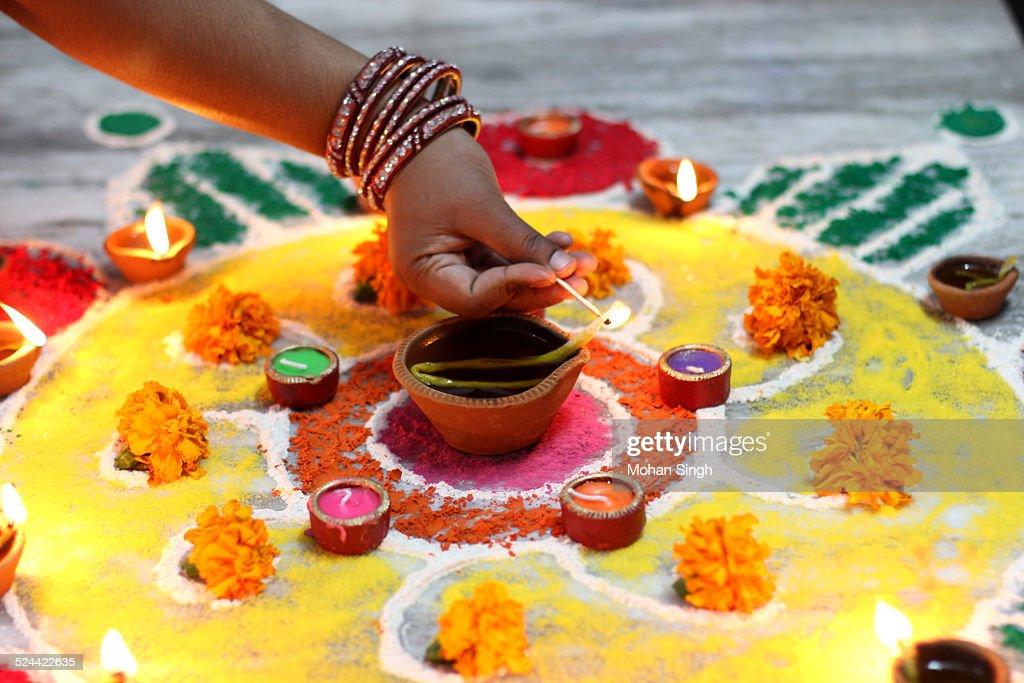 Indian woman lighting the lamp