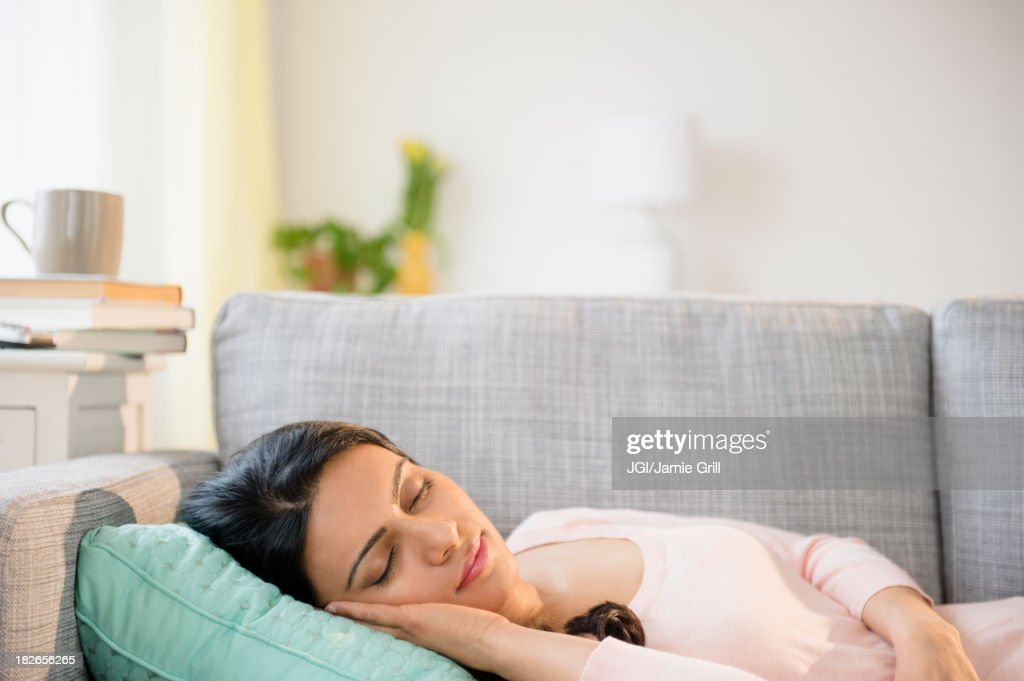 Indian woman napping on sofa : Stock Photo