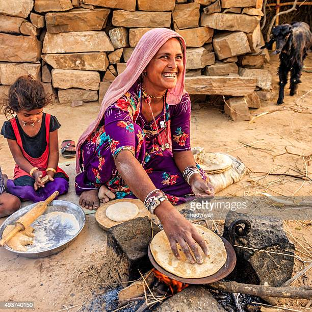 Indian woman preparing food - chapatti, flat bread, desert village