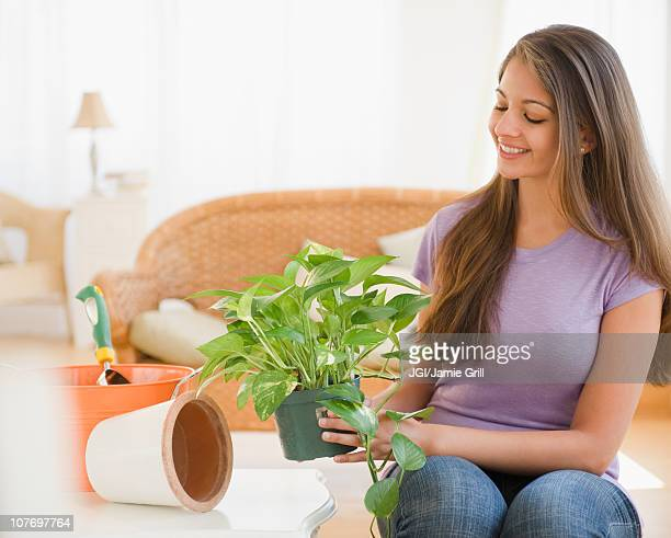 Indian woman putting house plant into pot