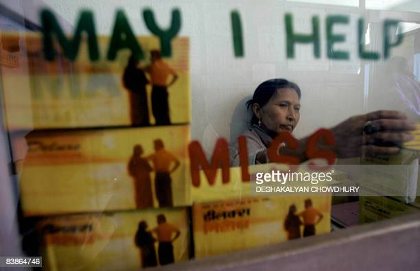Indian woman Radha Priya moves stock at a free condom distribution counter for sex workers at an office of the Meetei Leimarol Sinnai Sang a women's...
