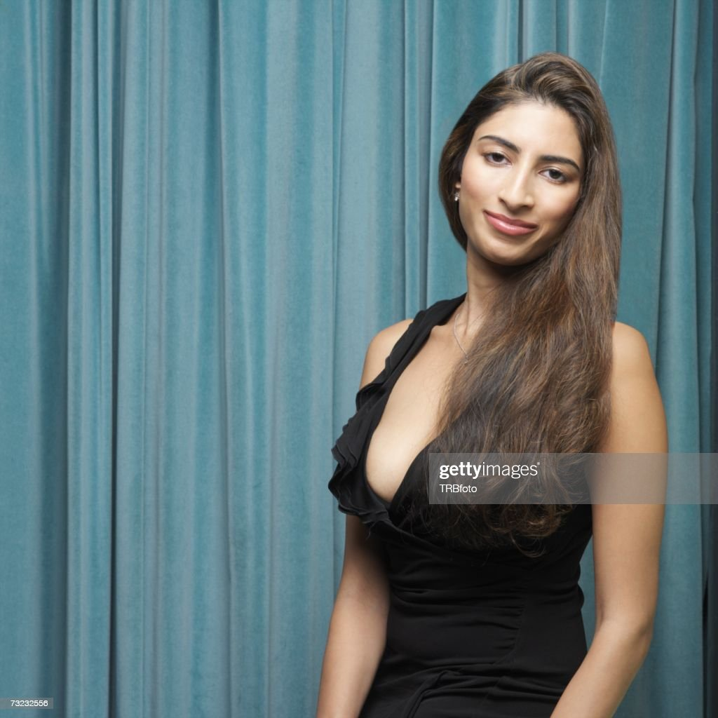 Indian woman smiling in front of curtain : Stock Photo