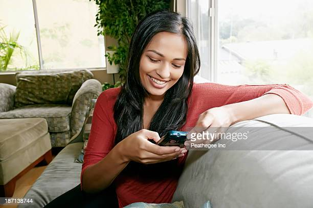 Indian woman using cell phone on sofa