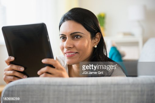 Indian woman using tablet computer on sofa : Stock Photo