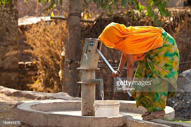 Indian woman villager pumping water from a well at Sawai Madhopur in Rajasthan Northern India