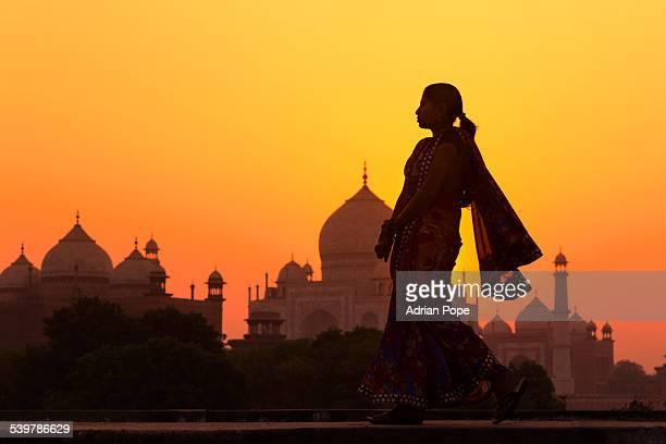 Indian woman walking at sunset near Taj Mahal