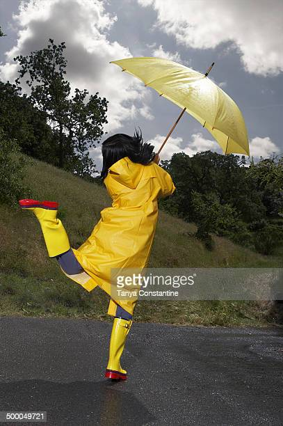 Indian woman wearing raincoat and rainboots with umbrella