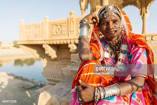Indian woman wearing traditional jewelry sitting near monument, Jaisalmer, Rajasthan, India