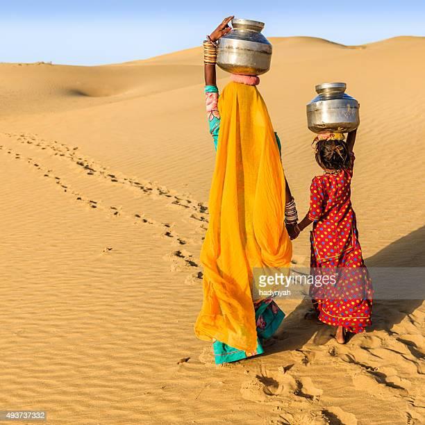 Indische Frau mit kleinen Tochter, die Wasser von gut