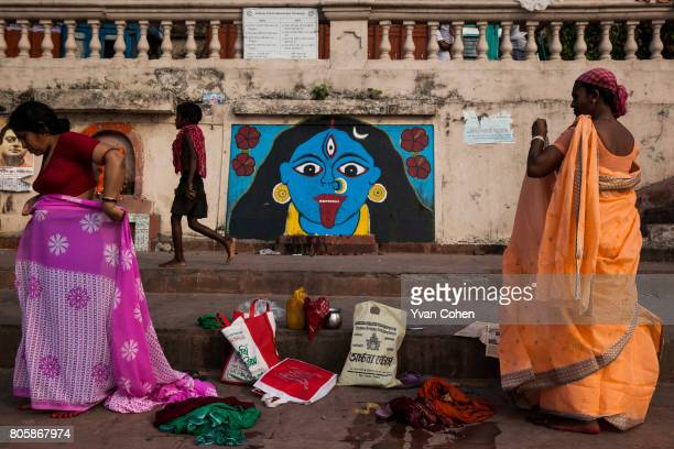 Indian women adjust their sarees after a ritual bath at a ghat on the banks of the Hooghly river a tributary of the Ganges that runs through Kolkata...
