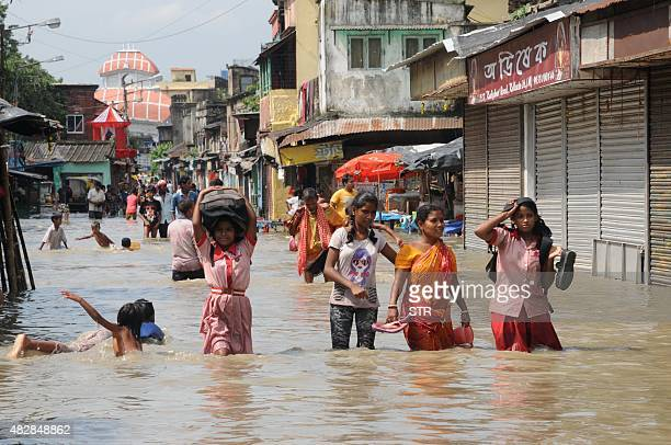 Indian women and children walk on a flooded street in Kolkata on August 3 2015 Parts of the eastern city were flooded as the river Ganges burst its...