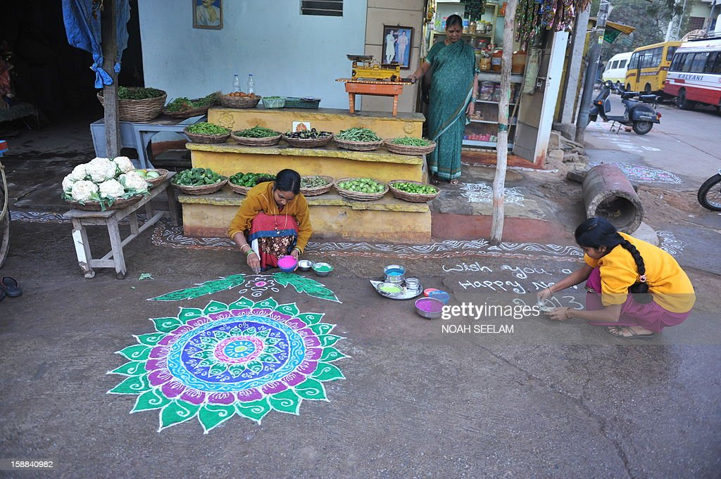 Indian women apply coloured powder to their 'rangolis', a Hindu ritual design, in front of their home in Hyderabad on January 1, 2013. Rangolis are drawn in front of homes early in the morning with a beautiful motif to welcome relatives and friends to mark the New Year. AFP PHOTO / Noah SEELAM
