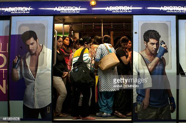 Indian women are framed in the doorway by advertisments for a men's deodorant as they travel in the carriage reserved for women on the metro in New...