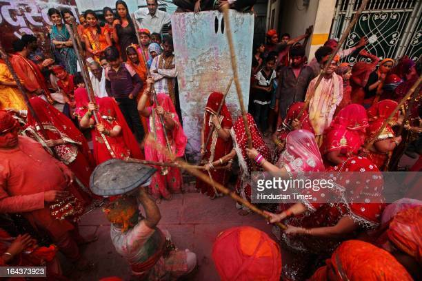 Indian women beat men with wooden sticks during the Lathmar Holi festival at the Nandji Temple in Nandgaon some 120 kms far from New Delhi on March...