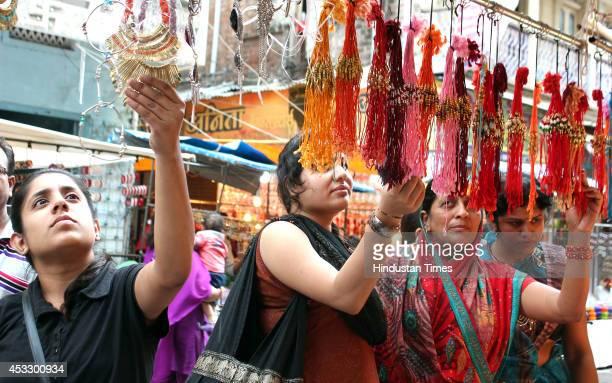 Indian women buy Rakhis ahead of Raksha Bandhan on August 7 2014 in Indore India The festival of Raksha Bandhan' or 'Rakhi' celebrate the...