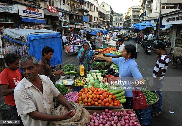 Indian women buy vegetables at a market in Mumbai on December 16 2013 India's inflation jumped to a 14monthhigh of 752 percent in November data...
