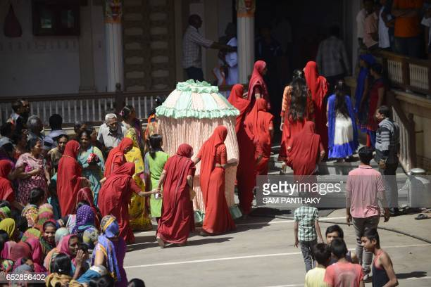 Indian women caretakers escort an unidentified covered female member from the priestly family of the Kalupur Swaminarayan Temple as she arrives to...