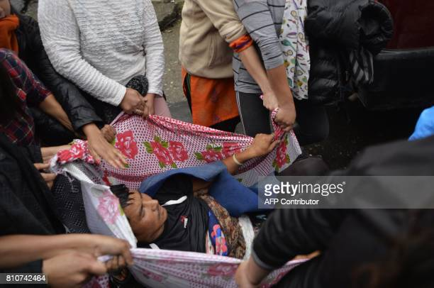 Indian women carry an injured man to Darjeeling hospital following clashes with Gorkhaland supporters during an indefinite strike called by Gorkha...