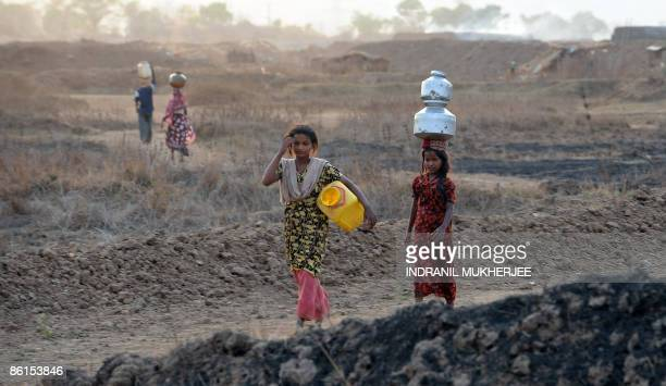 Indian women carry empty waterpots to fill drinking water from a municipal tap about two kilometers away from home at Kondgaon village of Raigad...