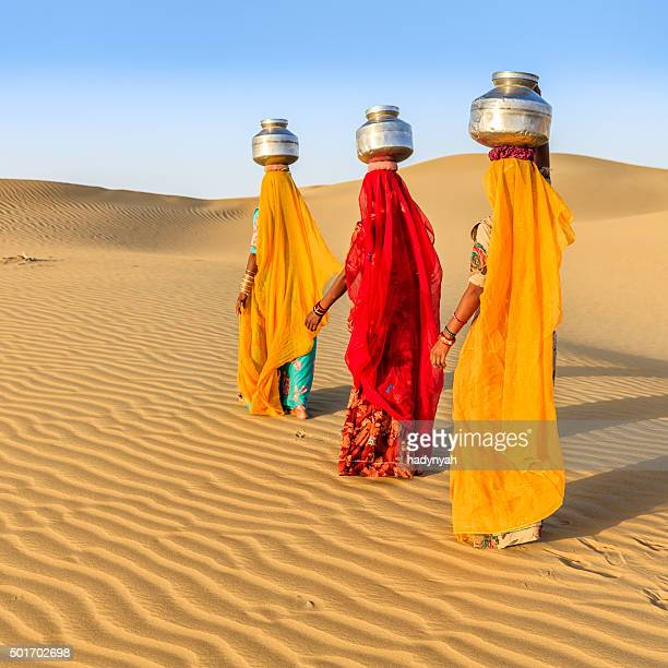 Indian women carrying on their heads water from local well