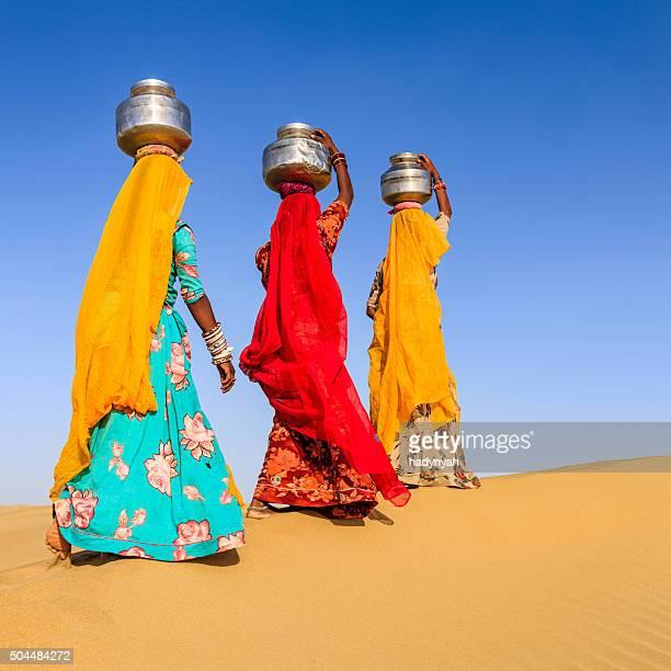 Las mujeres Indias llevar en la cabeza de local y agua
