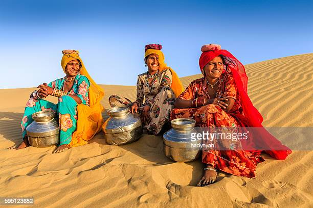 Indian women carrying water from local well, desert village, India