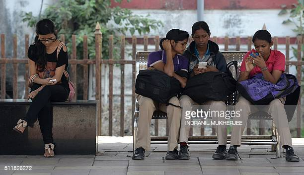 Indian women check their mobile telephones at a free WiFi Internet zone in Mumbai on February 23 2016 A village in Indian Prime Minister Narendra...