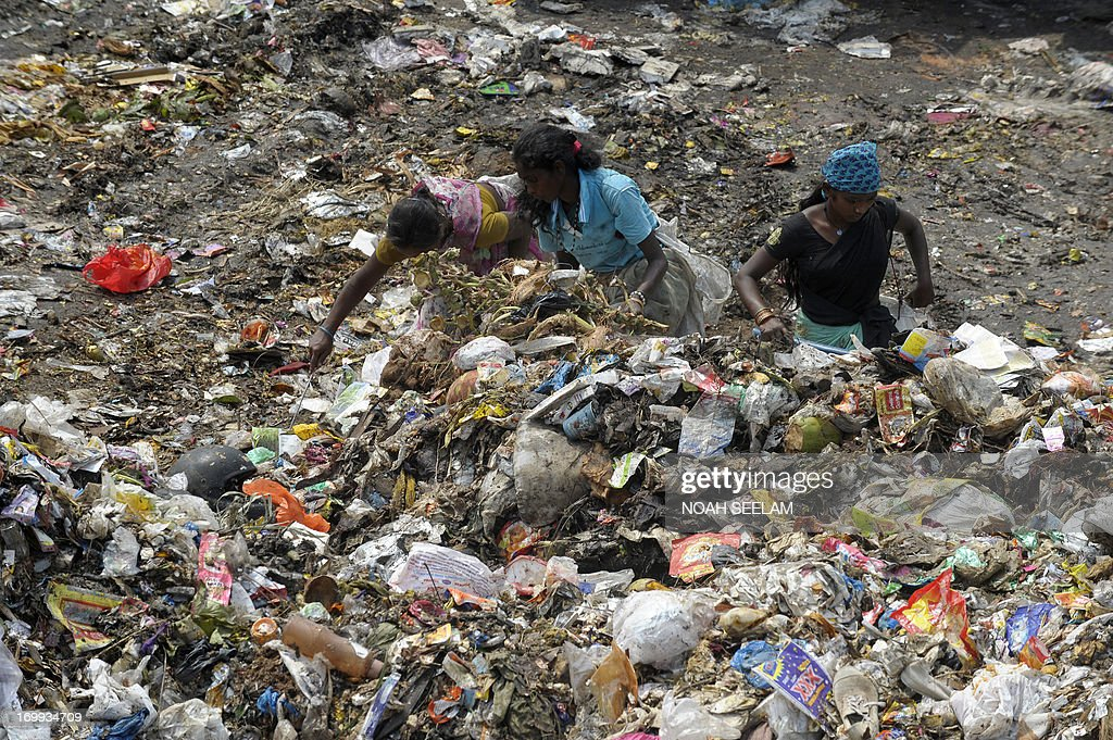 Indian women collect recyclable items at a garbage dump yard in Hyderabad on June 5, 2013, the World Environment Day. India's cities are becoming more polluted and unhealthy, according to a new survey showing growing concern about the impact of high economic growth on the environment. AFP PHOTO / Noah SEELAM