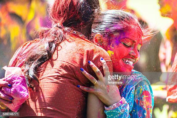 Indian women covered with holi powder hugging each other