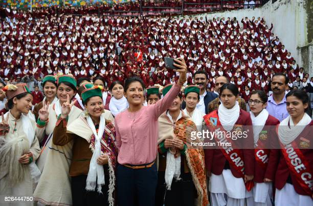 Indian women cricket team member Sushma Verma take picture with school girls during her visit of her old school Government senior secondary school...