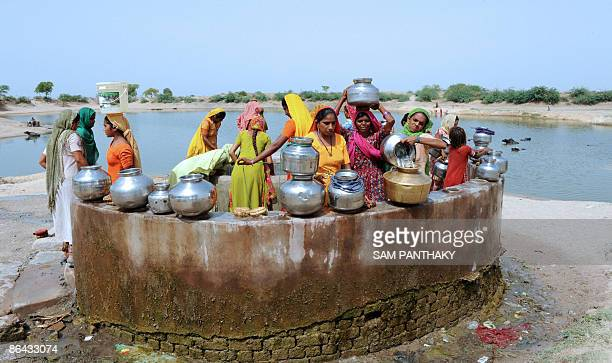 Indian women draw water from a well in the village of Kayla some 65kms from Ahmedabad on May 5 2009 India�s huge and growing population is putting a...