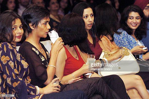 Indian women dressed in the latest fashion outfits have drinks during a party held prior to a fashion show in New Delhi 17 September 2004 The...