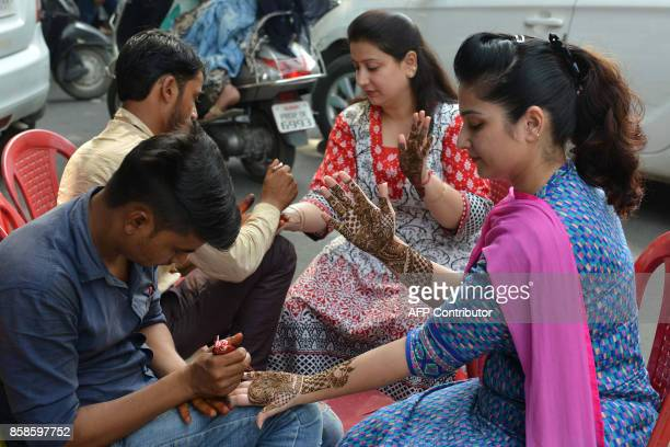 Indian women get her hands decorated with henna on the eve of 'Karva Chauth' festival known as Husband's day in Amritsar on October 7 2017 During...