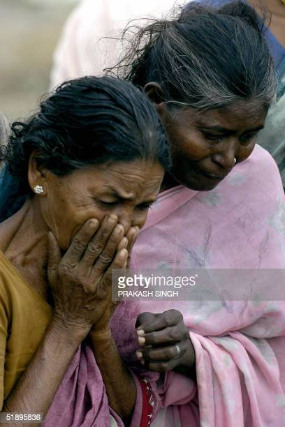 Indian women grieve as they witness bodies being placed into a mass burial site in Cuddaloresome 185 kms south of Madras 27 December 2004 after tidal...
